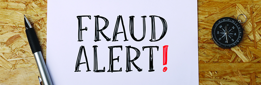 fraud alert note on wooden table