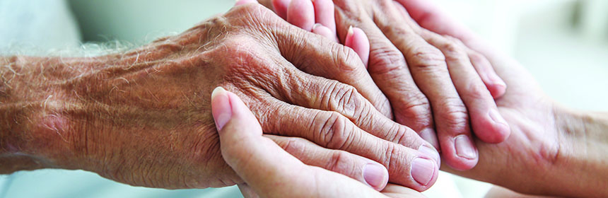 young woman holding older person hands