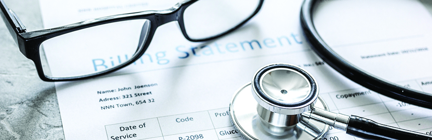 medical bill with stethoscope on table